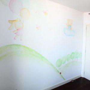 Mural infantil pintado a mano con dibujo de conejita con globos de colores, nube y prado con mariquitas en efecto acuarela, diseño de La que pinta en Barcelona.