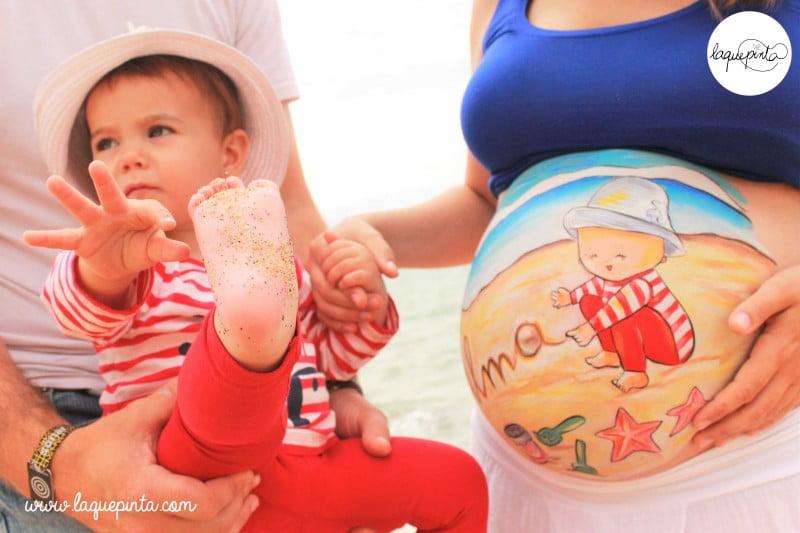Body painting para embarazada de La que pinta con dibujo de bebé escribiendo en la arena de la playa