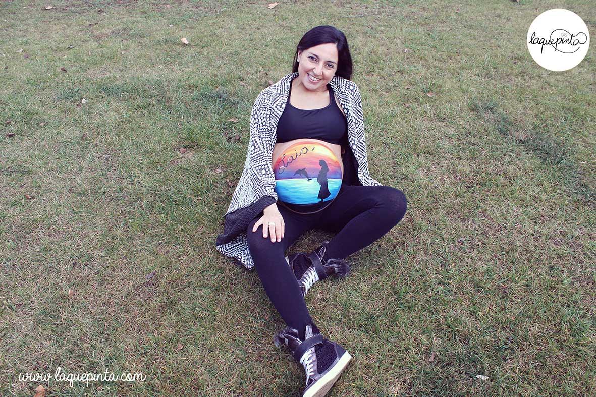 Body painting para embarazada con barriga pintada con dibujo de embarazada cerca de un atardecer en el mar y sesión de fotos de recuerdo de La que pinta en Barcelona
