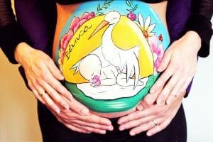 Body painting para embarazada con barriga pintada con dibujo de cigüena y bebé de La que pinta con barriga pintada con dibujo de bebé mediantando de La que pinta en Barcelona