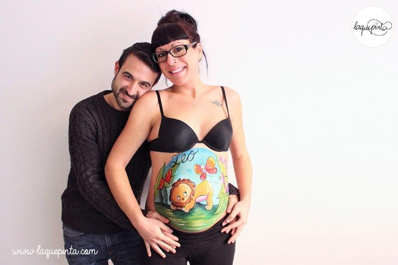 Body painting para embarazada con barriga pintada con dibujo de león jugando con mariposa en la selva y sesión de fotos de recuerdo de La que pinta en Barcelona