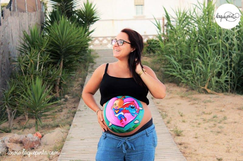 Body painting para embarazada con barriga pintada con dibujo de cigüena y bebé de La que pinta con barriga pintada con dibujo de Súper bebé y Coco de La que pinta en Barcelona