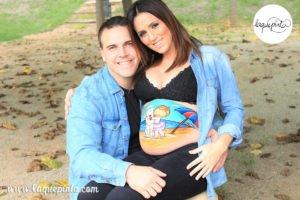 Belly painting con dibujo de bebé bailarina y mascota de la familia abrazados en la playa