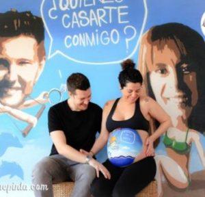 Sesión de belly painting con dibujo en la barriga de la embarazada a domicilio, con dibujo 100% personalizado de bebé tirándose en paracaidas a juego con el mural de pedida de matrimonio de la pareja, de La que pinta.
