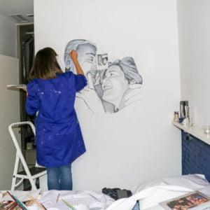 Mural pintado a mano por La que pinta en Barcelona con retrato de pareja acariciándose.
