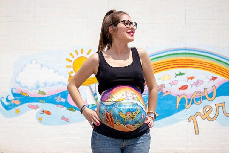 Barriga pintada con dibujo de bebé surfeando de La que pinta Barcelona