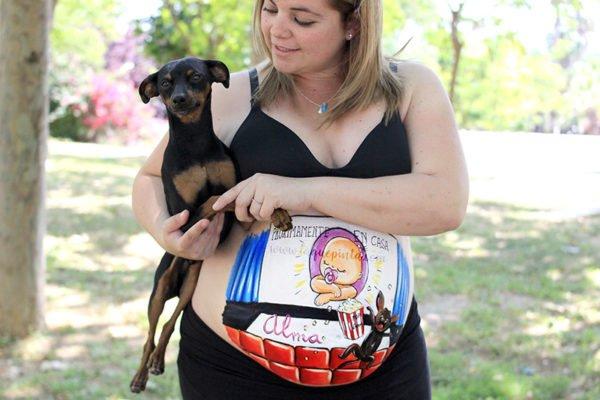 Niña en el cine con mascota en barriga pintada