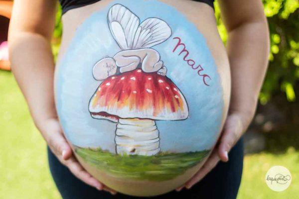 Belly painting bebé alado en una seta