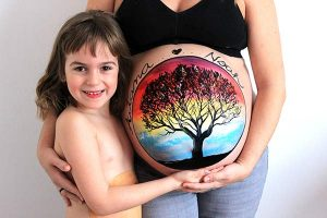Belly painting de familia de árbol en cielo multicolor
